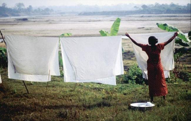 Nepali Woman Hanging Sheets to Dry by Flickr User Matthew Ramsey, CC License = Attribution