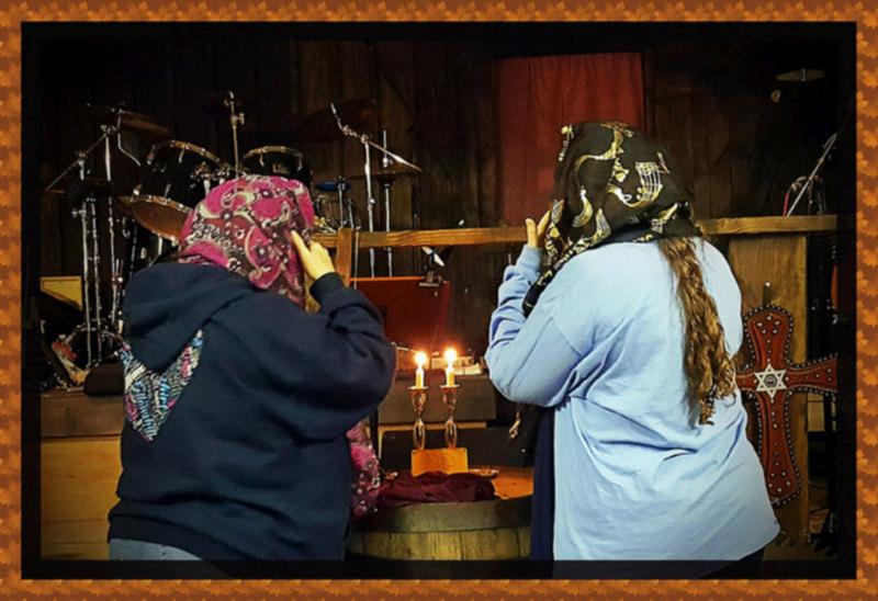 women praying at cowboy church on a friday